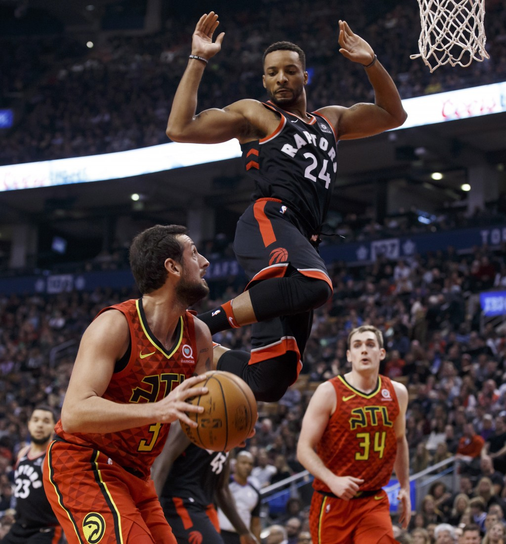 Toronto Raptors forward Norman Powell (24) jumps while defending Atlanta Hawks guard Marco Belinelli (3) during the first half of an NBA basketball ga...