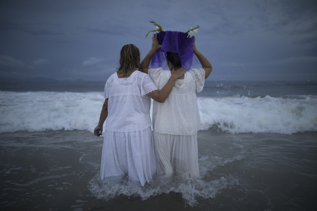 A faithful carries flowers as an offering for Yemanja, goddess of the sea, during a ceremony that is part of traditional New Year's celebrations on Co...