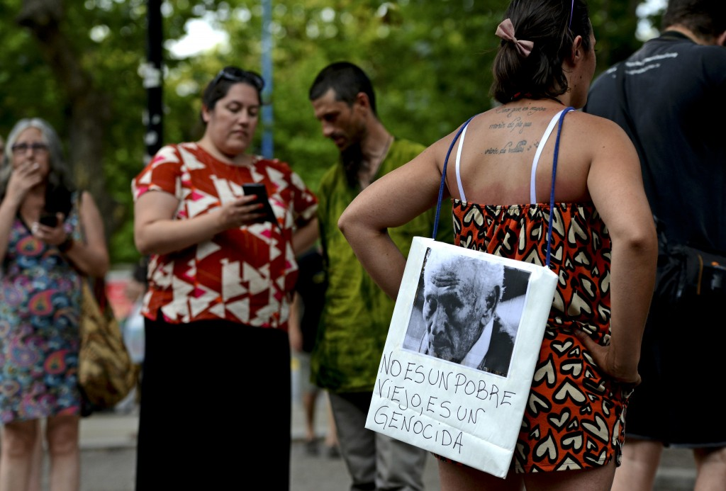"A woman stands with a picture of former police officer Miguel Etchecolatz that reads in Spanish, ""He is not a poor man, he is a genocide"" during a pro..."