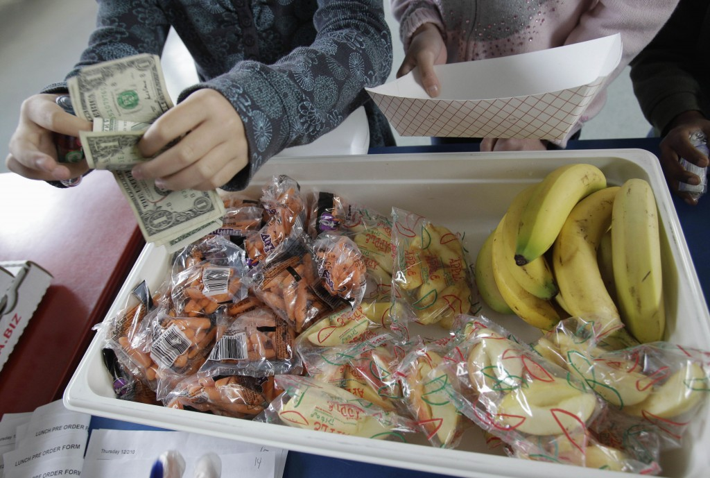 FILE - In this Dec. 2, 2010, file photo, a student at Fairmeadow Elementary School pays for lunch consisting of fruits and vegetables during a school ...