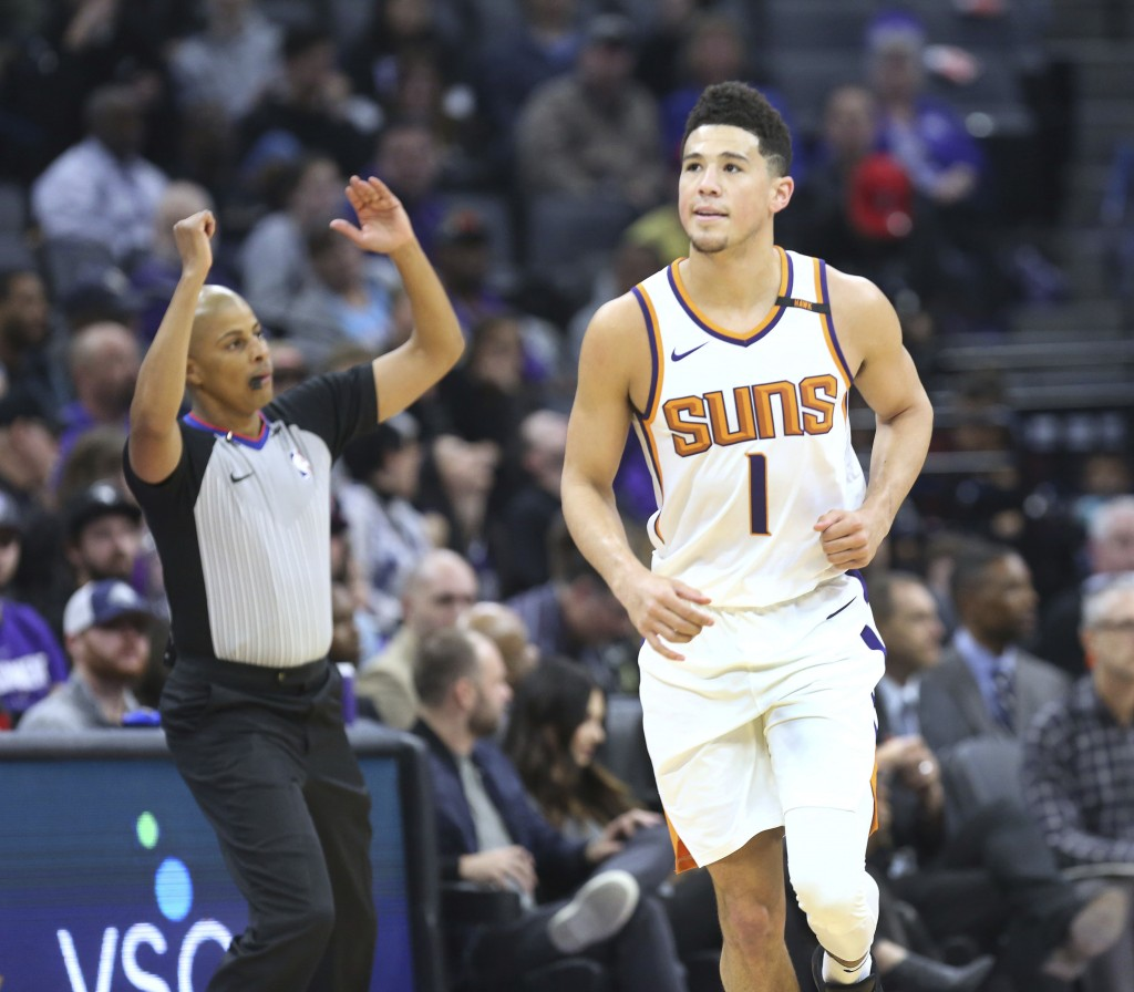Phoenix Suns guard Devin Booker (1) reacts after hitting a three-point shot during the first half of an NBA basketball game against the Sacramento Kin...