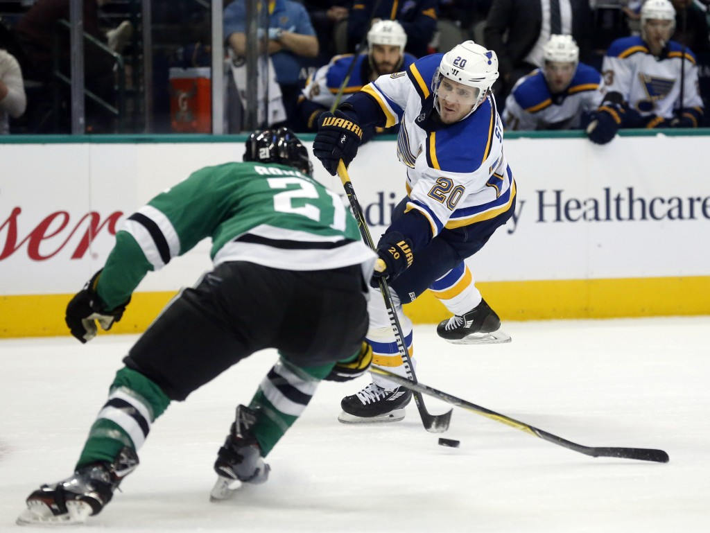 St. Louis Blues left wing Alexander Steen (20) shoots the puck past Dallas Stars left wing Antoine Roussel (21) during the second period of an NHL hoc...