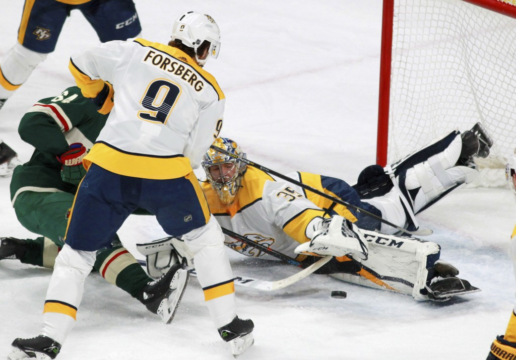 Minnesota Wild's Mikael Granlund (64), of Finland, is denied at the goal by Nashville Predators Pekka Rinne (35), of Finland, in front of Filip Forsbe...