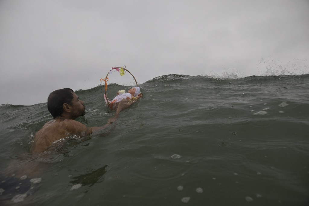 A man sends a basket with a doll into the waters of Copacabana beach as an offering for Yemanja, goddess of the sea, in Rio de Janeiro, Brazil, Friday...