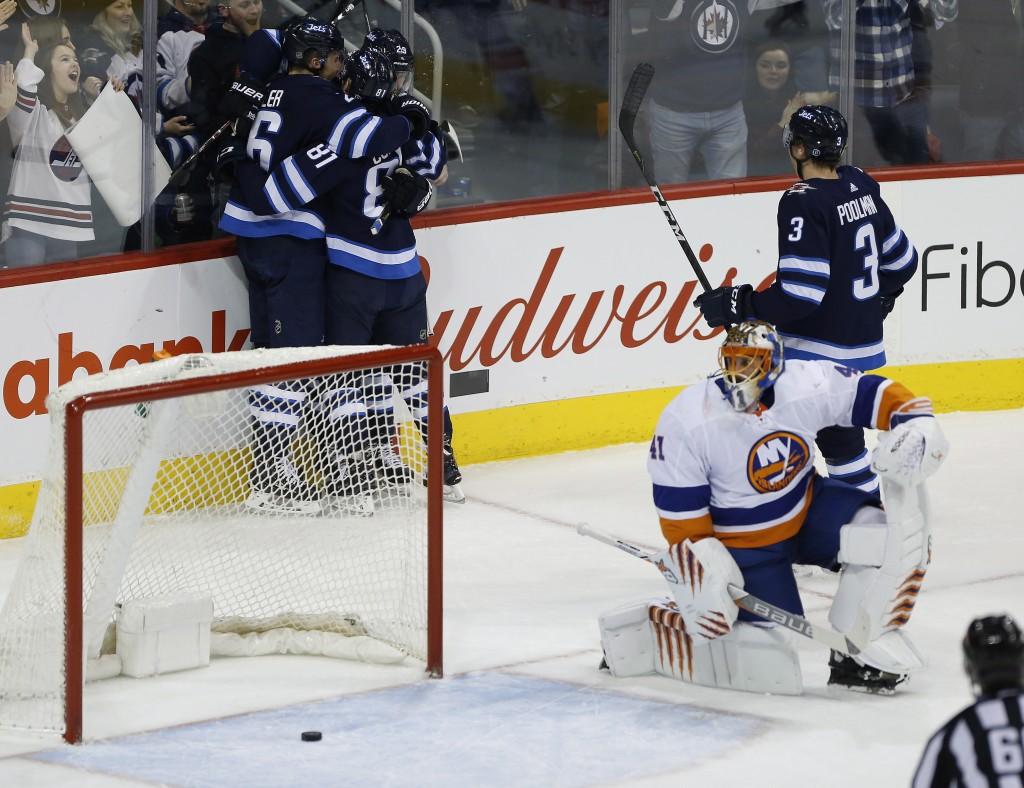 Winnipeg Jets' Blake Wheeler (26), Kyle Connor (81), Patrik Laine (29) and Tucker Poolman (3) celebrate Wheeler's goal as New York Islanders goalie Ja...