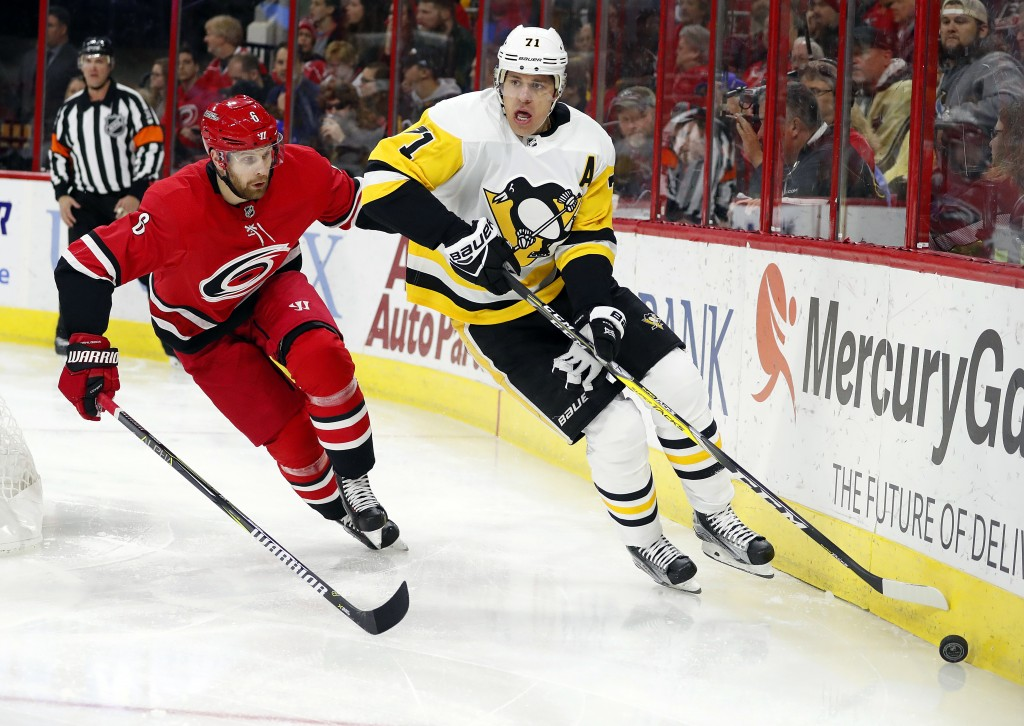Pittsburgh Penguins' Evgeni Malkin (71) reaches for the puck as Carolina Hurricanes' Klas Dahlbeck (6) defends during the first period of an NHL hocke...