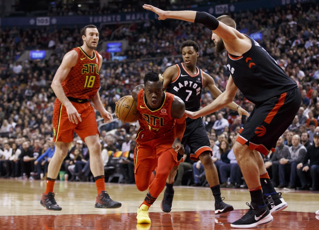 Toronto Raptors' Jonas Valanciunas, right, defends as Atlanta Hawks guard Dennis Schroeder (17) drives to the net during the first half of an NBA bask...