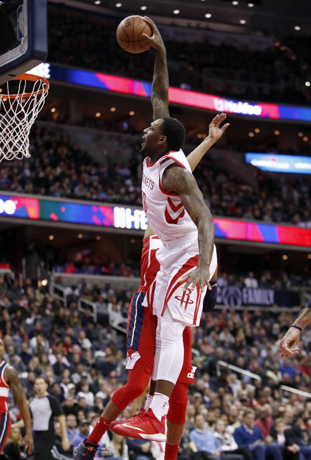 Houston Rockets forward Tarik Black (28) dunks past Washington Wizards forward Otto Porter Jr. during the first half of an NBA basketball game Friday,...