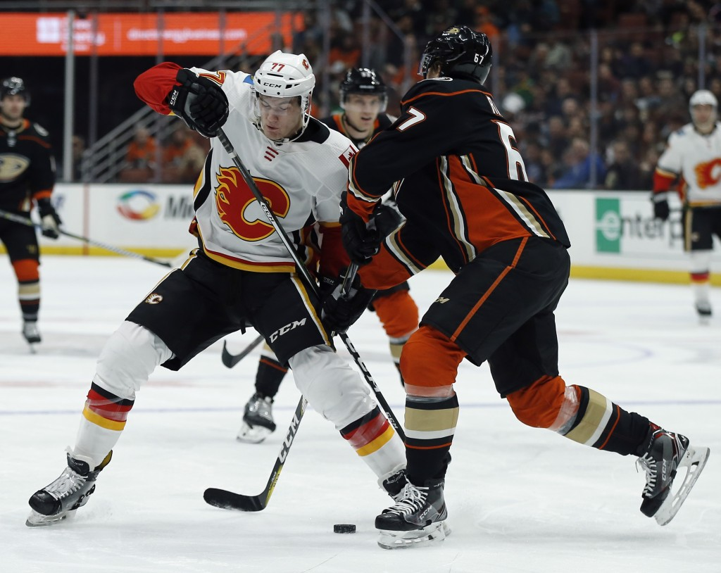 Anaheim Ducks center Rickard Rakell, right, of Sweden, blocks out Calgary Flames center Mark Jankowski (77) from advancing the puck during the first p...