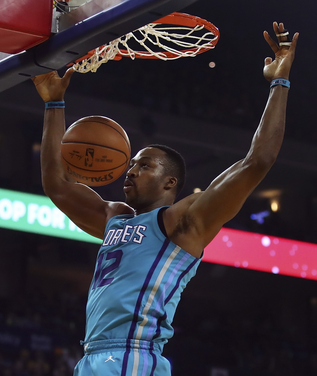 Charlotte Hornets' Dwight Howard scores against the Golden State Warriors during the first half of an NBA basketball game Friday, Dec. 29, 2017, in Oa...