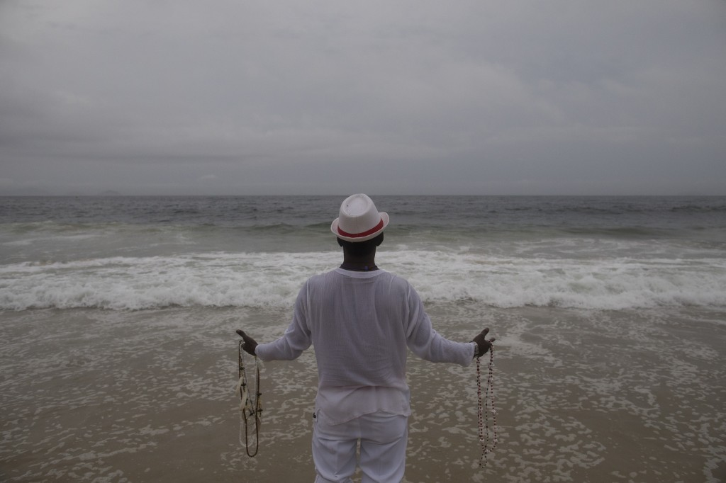 A man prays as he holds necklaces, as symbols of protection, during a ceremony for Yemanja, goddess of the sea, that is part of traditional New Year's...