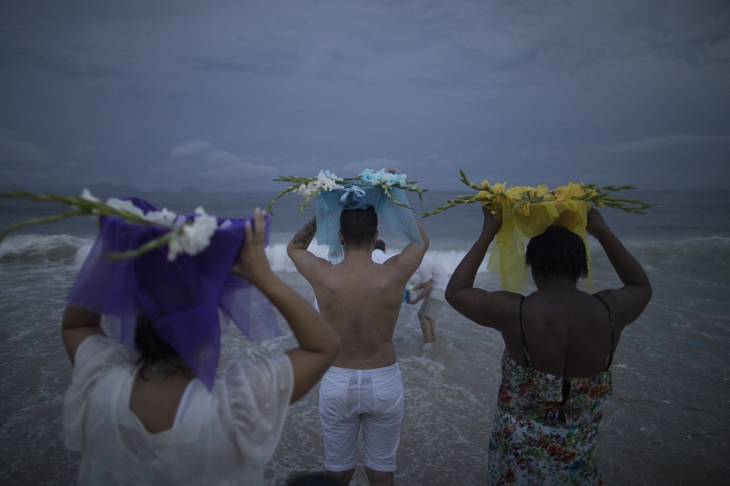 The faithful carry offerings for Yemanja, goddess of the sea, during a ceremony that is part of traditional New Year's celebrations on Copacabana beac...