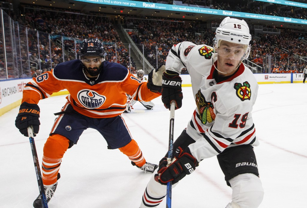 Chicago Blackhawks' Jonathan Toews (19) and Edmonton Oilers' Jujhar Khaira (16) work for the puck during the second period of an NHL hockey game Frida...