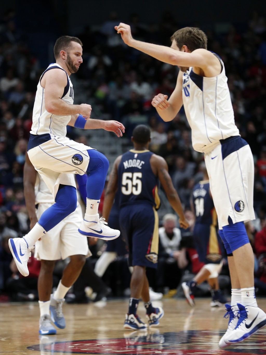 Dallas Mavericks guard J.J. Barea, left, celebrates with forward Dirk Nowitzki in the second half of an NBA basketball game in New Orleans, Friday, De...