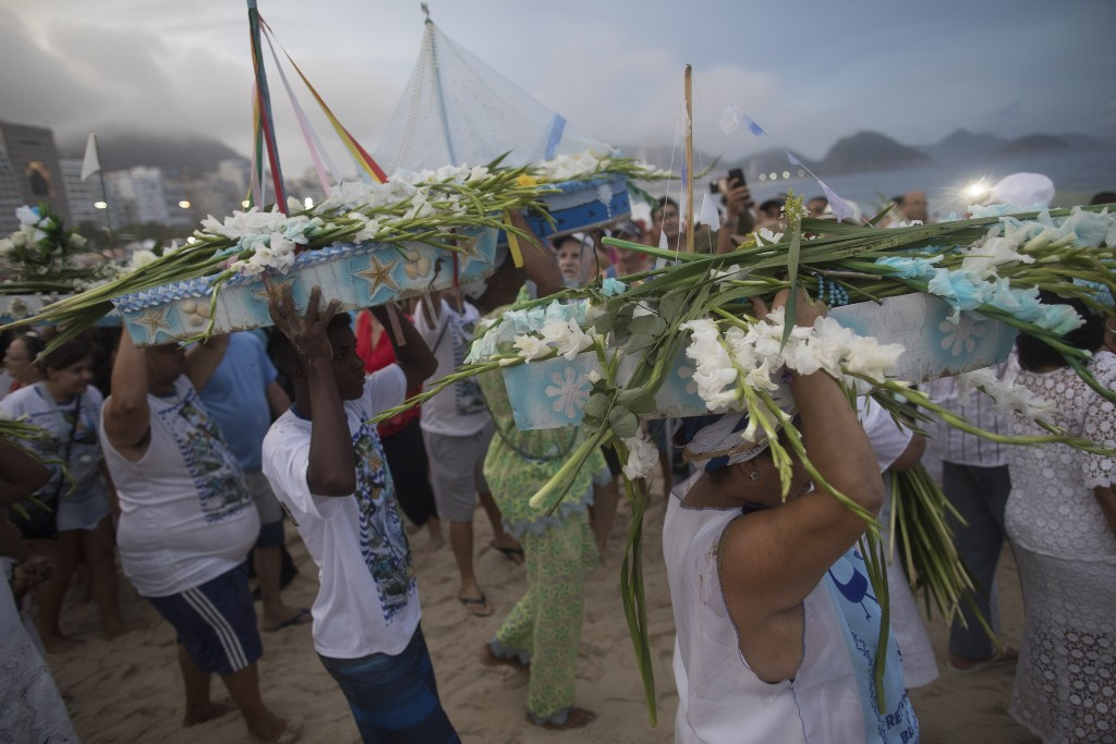 People carry small-scaled boats filled with flowers into the waters of Copacabana beach as an offering for Yemanja, goddess of the sea on Copacabana b...