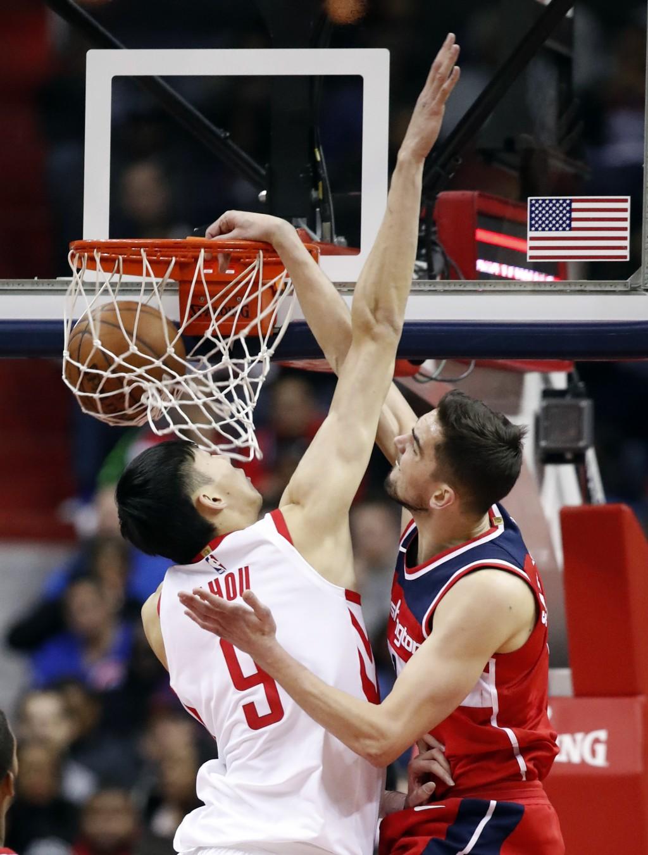 Washington Wizards forward Tomas Satoransky (31), from the Czech Republic, dunks over Houston Rockets forward Zhou Qi (9) during the first half of an ...