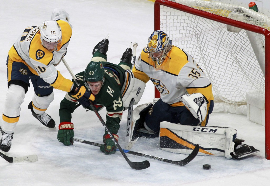 Minnesota Wild's Tyler Ennis (63) tripped up at the goal by Nashville Predators Colton Sissons (10) and Pekka Rinne (35), of Finland, during the first...