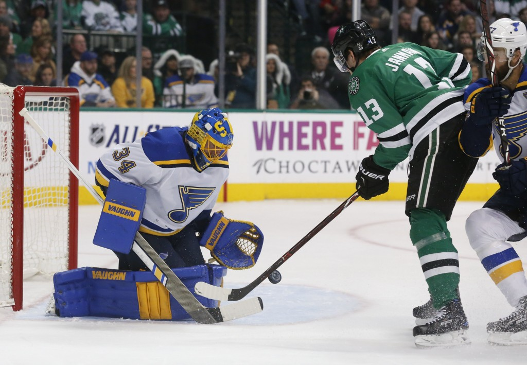 St. Louis Blues goaltender Jake Allen (34) makes a save on a shot by Dallas Stars center Mattias Janmark (13) during the first period of an NHL hockey...
