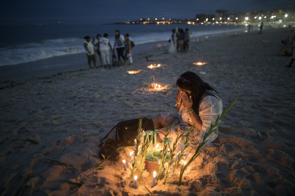 A faithful prays for Yemanja, goddess of the sea, during a ceremony that is part of traditional New Year's celebrations on Copacabana beach, in Rio de...