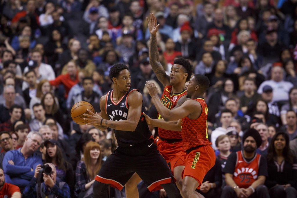 Toronto Raptors guard DeMar DeRozan (10) is defended by Atlanta Hawks' John Collins (20) and Isaiah Taylor (22) during the first half of an NBA basket...