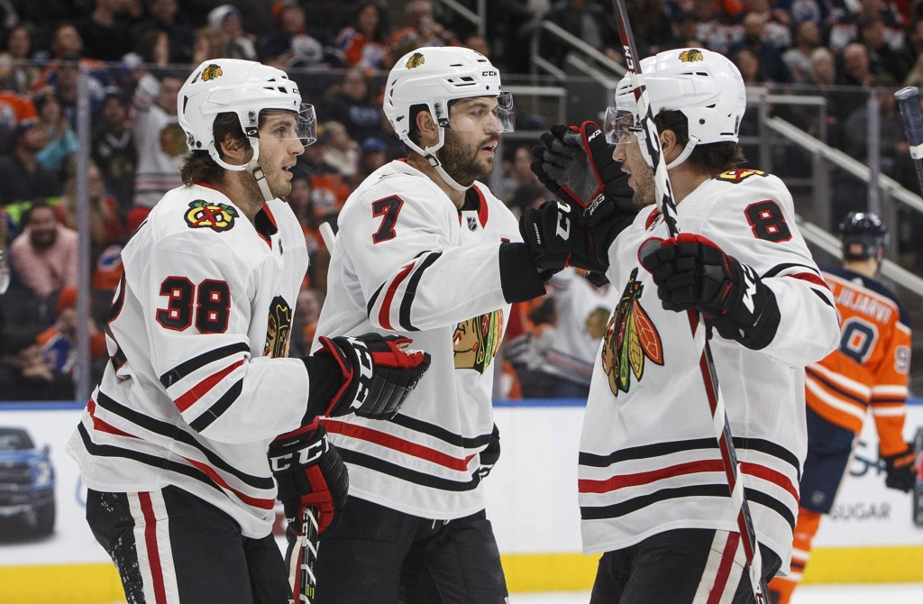 Chicago Blackhawks' Ryan Hartman (38), Brent Seabrook (7) and Nick Schmaltz (8) celebrate a goal against the Edmonton Oilers during the first period o...