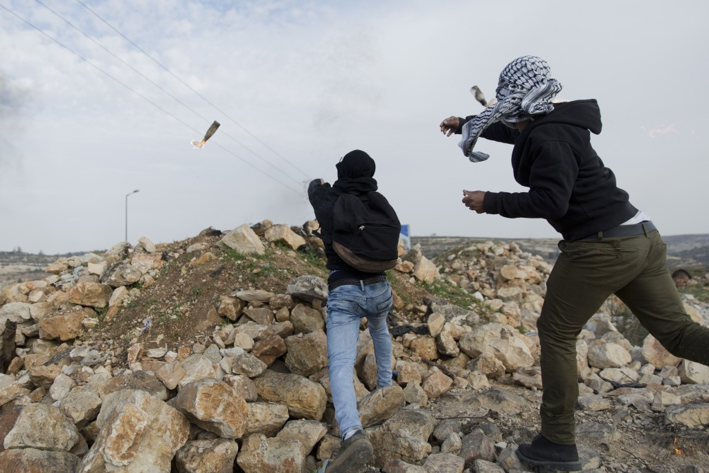 Two Palestinian protesters throw Molotov cocktail toward Israeli troops during clashes following protests against U.S. President Donald Trump's decisi...