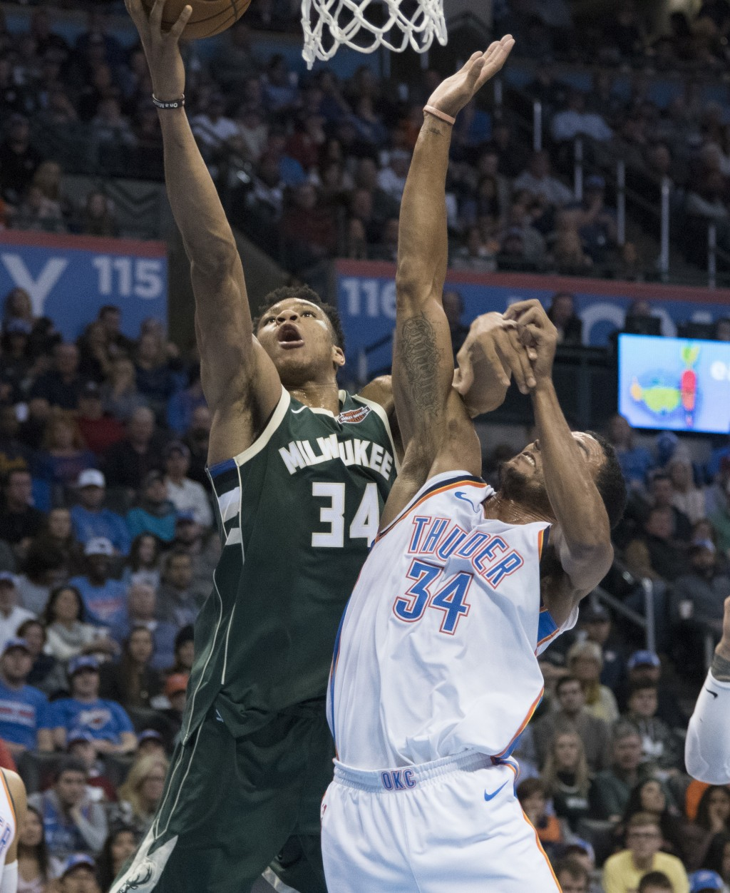 Milwaukee Bucks forward Giannis Antetokounmpo (34) and Oklahoma City Thunder forward Josh Huestis (34) battle for the ball during the first half of an...