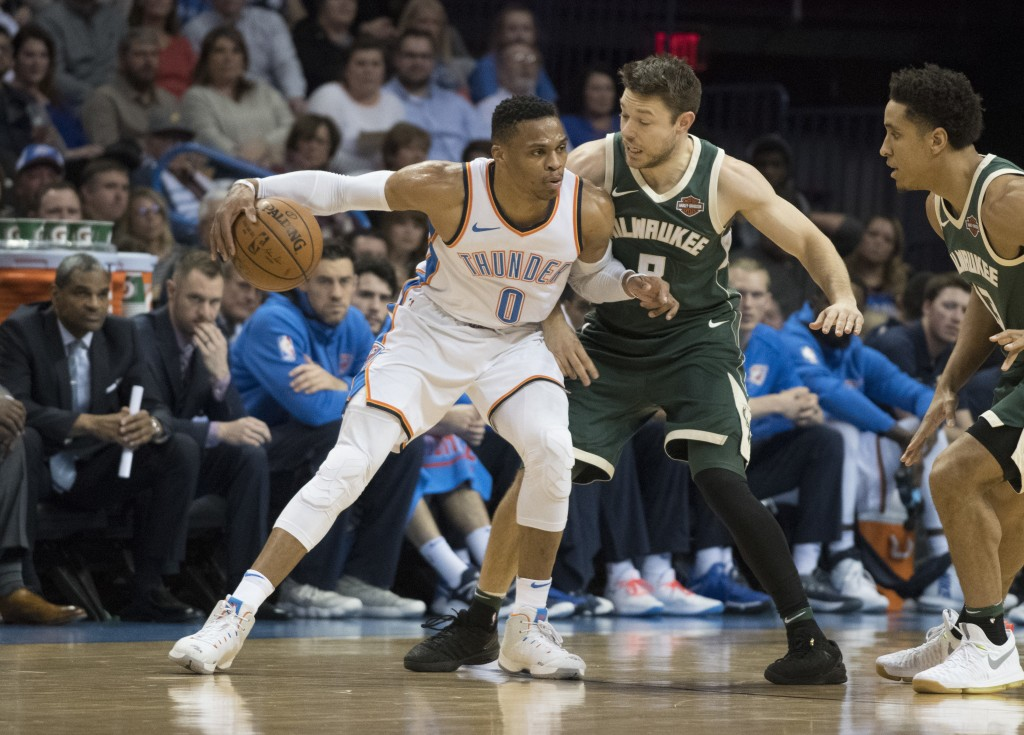 Oklahoma City Thunder guard Russell Westbrook (0) drives around Milwaukee Bucks guard Matthew Dellavedova (8) during the first half of an NBA basketba...