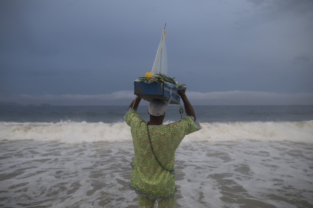A faithful carries a small-scaled boat filled with offerings for Yemanja, goddess of the sea, during a ceremony that is part of traditional New Year's...