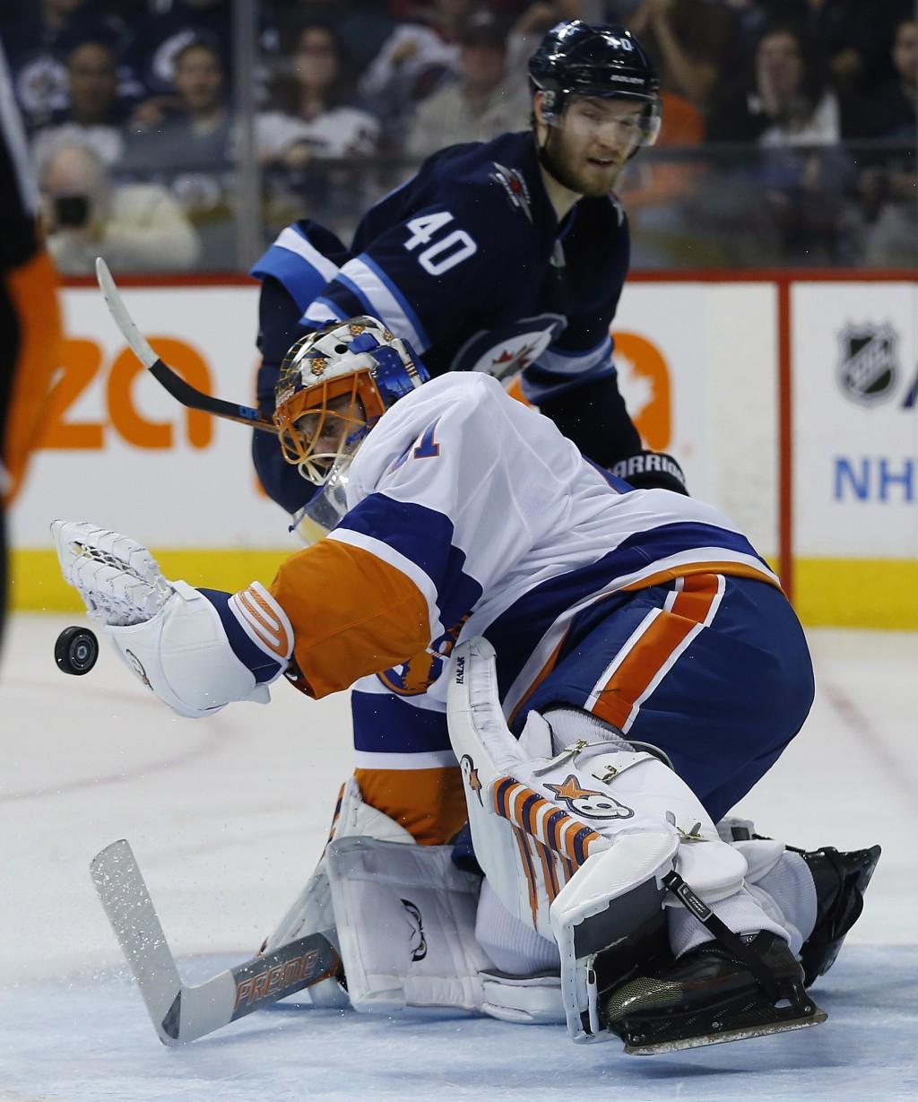 New York Islanders goalie Jaroslav Halak (41) saves the breakaway attempt by Winnipeg Jets' Joel Armia (40) during second-period NHL hockey game actio...