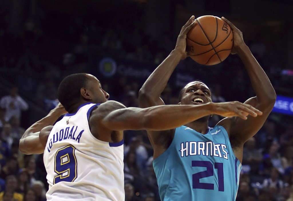 Charlotte Hornets' Treveon Graham, right, shoots against Golden State Warriors' Andre Iguodala (9) during the first half of an NBA basketball game Fri...