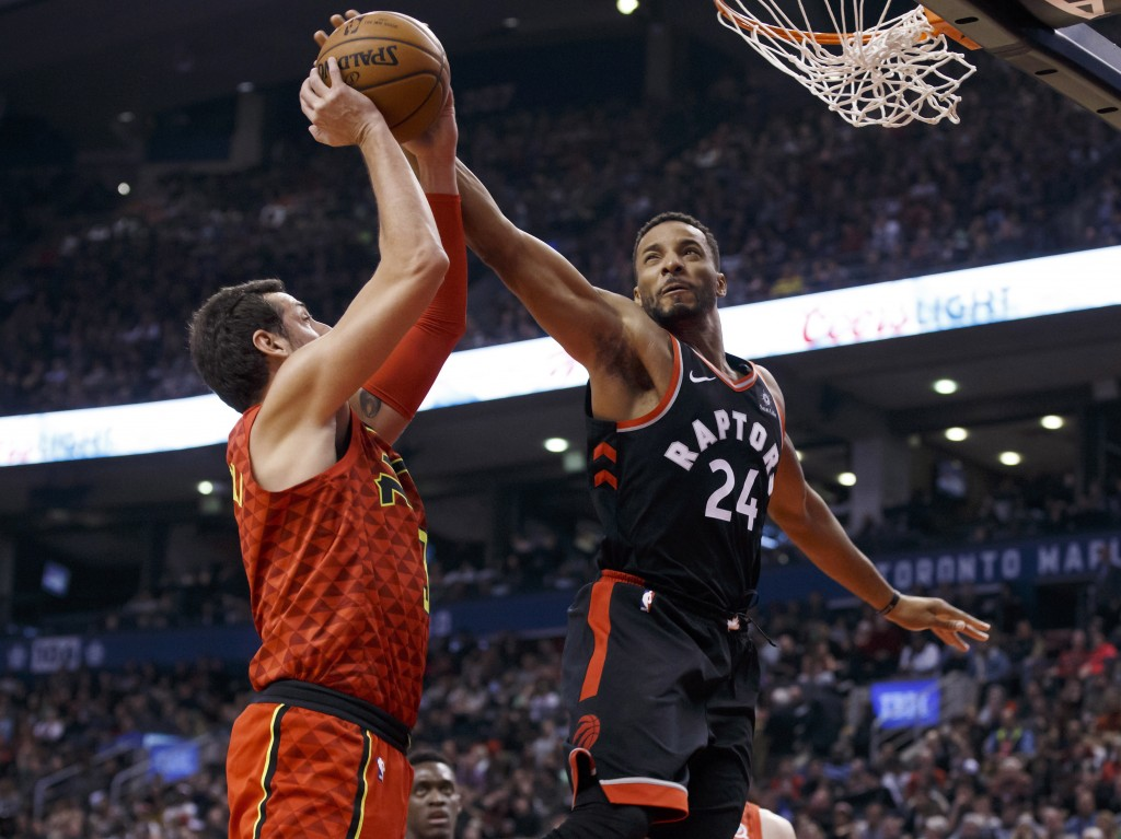 Toronto Raptors forward Norman Powell (24) blocks a shot by Atlanta Hawks guard Marco Belinelli (3) during the first half of an NBA basketball game Fr...