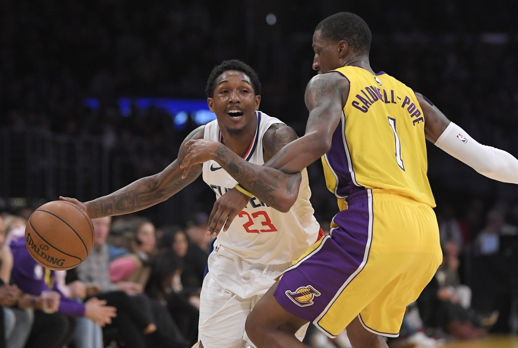 Los Angeles Clippers guard Lou Williams, left, tires to dribble past Los Angeles Lakers guard Kentavious Caldwell-Pope during the first half of an NBA...