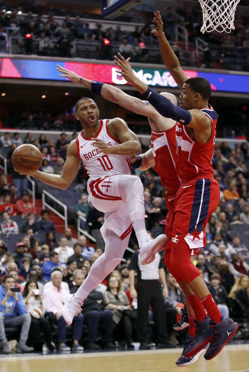 Houston Rockets guard Eric Gordon (10) passes the ball as he is guarded by Washington Wizards center Marcin Gortat (13), from Poland, and forward Otto...