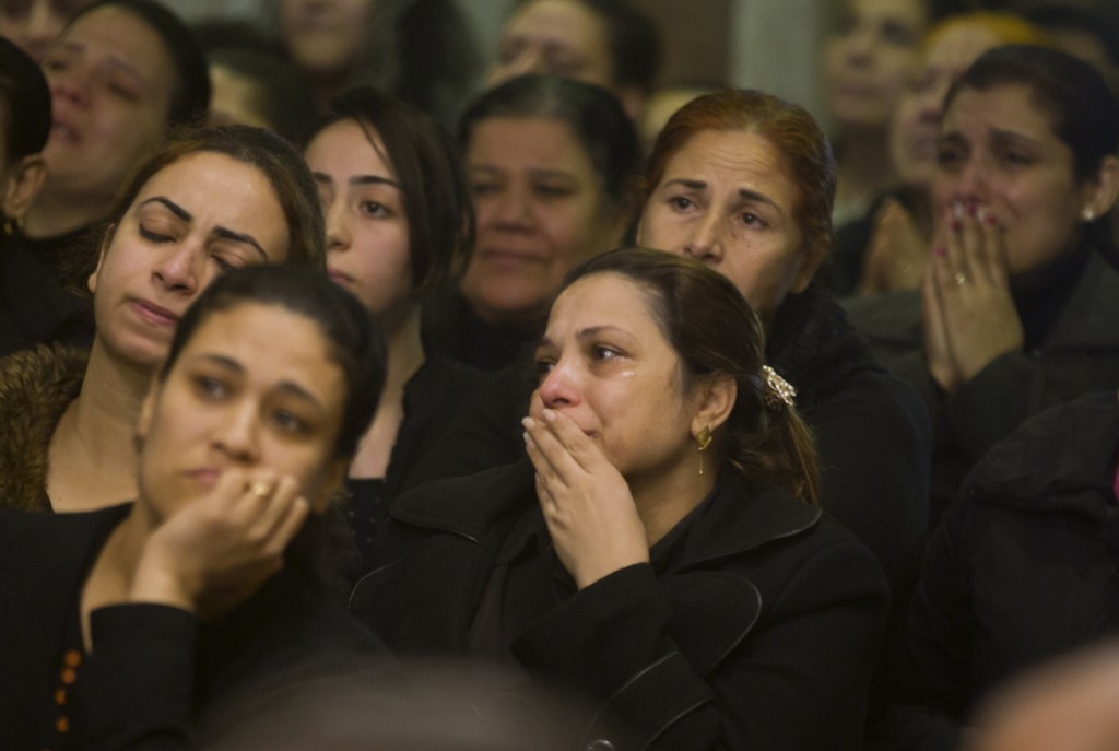Relatives of Coptic Christians grieve as during the funeral service of victims of the attacked on Mar Mina church in Cairo, Egypt, Friday, Dec. 29, 20...