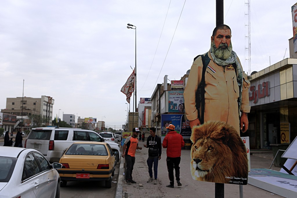 In this Sunday, Nov. 26, 2017 photo, people pass by a poster of Ali Jayad al-Salhi, 65, a volunteer with Popular Mobilization Forces killed fighting I...
