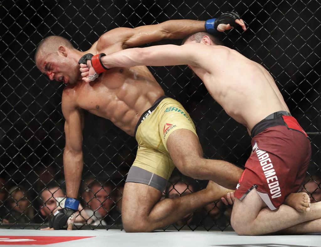 Khabib Nurmagomedov, right, hits Edson Barboza in a lightweight mixed martial arts bout at UFC 219, Saturday, Dec. 30, 2017, in Las Vegas. (AP Photo/J...