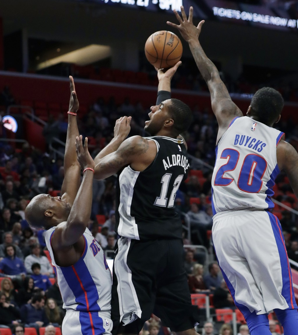 San Antonio Spurs forward LaMarcus Aldridge (12) shoots over Detroit Pistons forward Anthony Tolliver (43) and guard Dwight Buycks (20) during the fir...