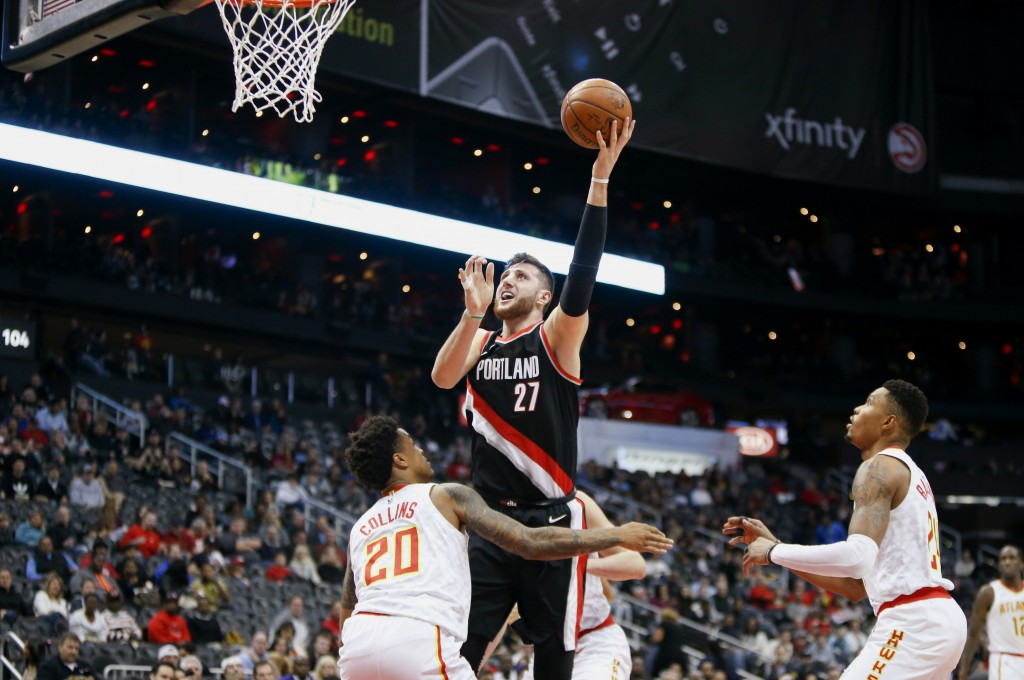 Portland Trail Blazers center Jusuf Nurkic (27) shoots over Atlanta Hawks forward John Collins (20) as guard Kent Bazemore (24) looks on in the first ...
