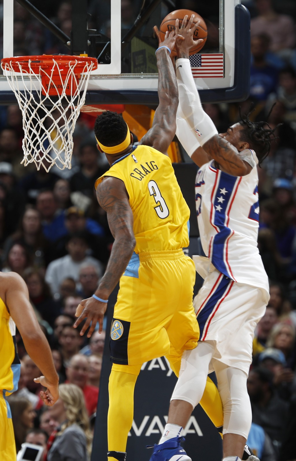 Denver Nuggets guard Torrey Craig, left, fouls Philadelphia 76ers forward Richaun Holmes as he goes up for a basket in the first half of an NBA basket...