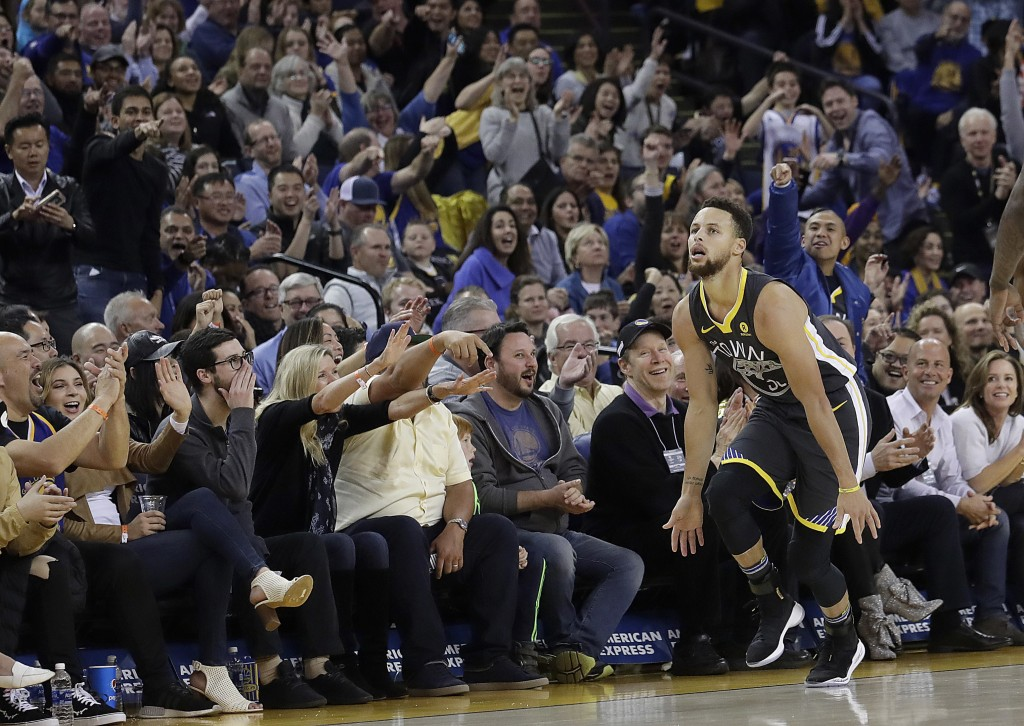 Golden State Warriors guard Stephen Curry celebrates in front of fans after scoring against the Memphis Grizzlies during the first half of an NBA bask...