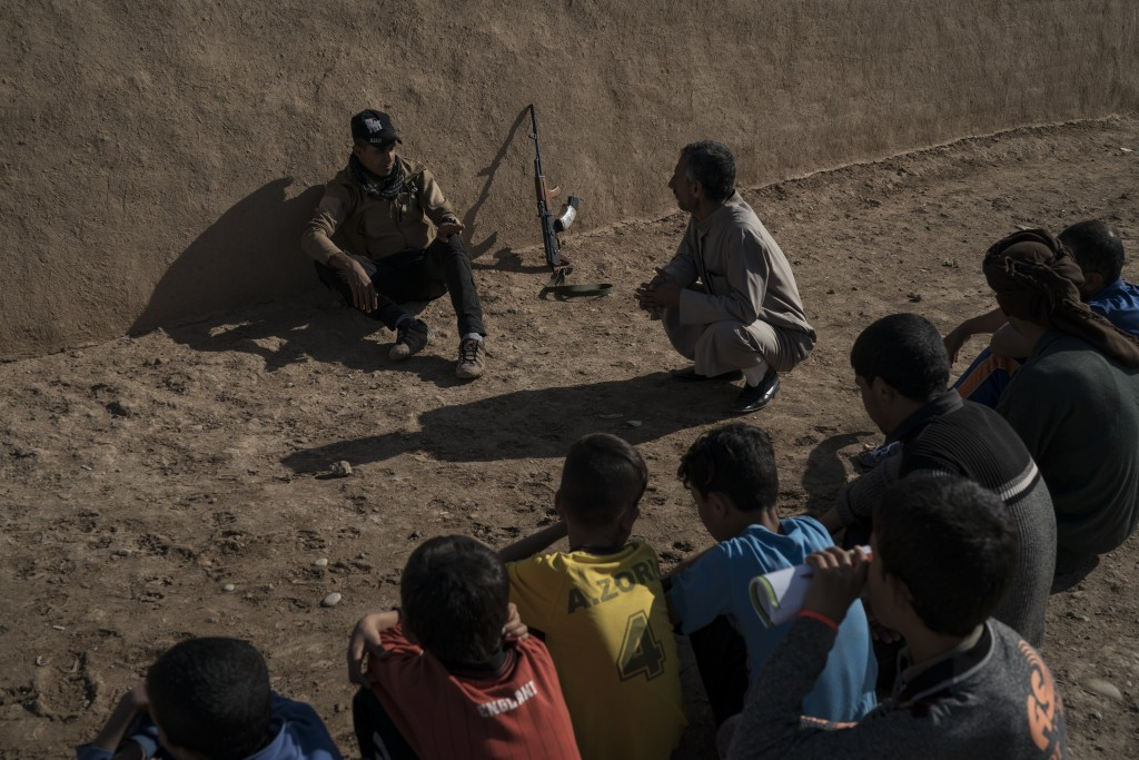 In this Nov. 12, 2017 photo, a local fighter talks with residents of the Bijwaniya village, south of Mosul, Iraq. Five young men were taken by unident...