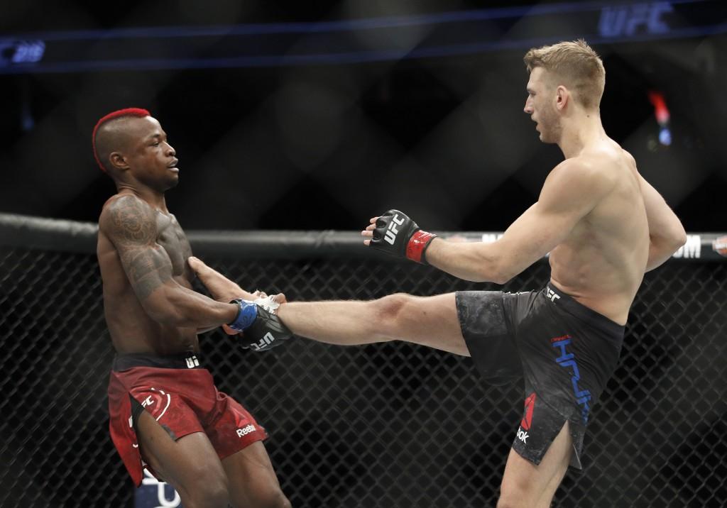 Dan Hooker, right, fights Marc Diakiese in a lightweight mixed martial arts bout at UFC 219, Saturday, Dec. 30, 2017, in Las Vegas. (AP Photo/John Loc...