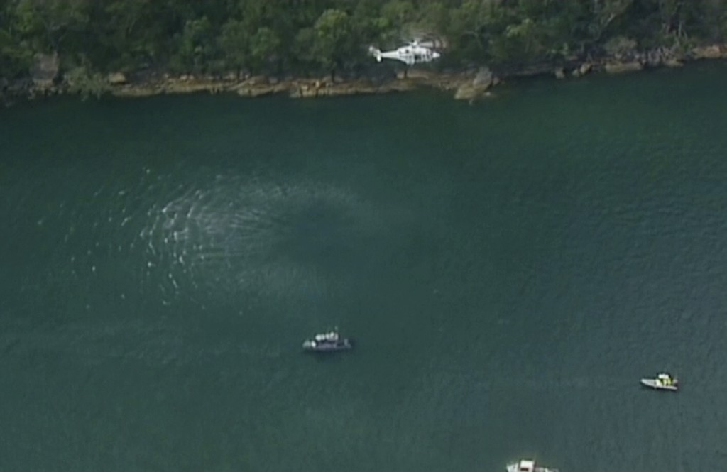 In this image made from a video, a search and rescue helicopter flies above search boats in Hawkesbury River, New South Wales, Australia Sunday, Dec. ...