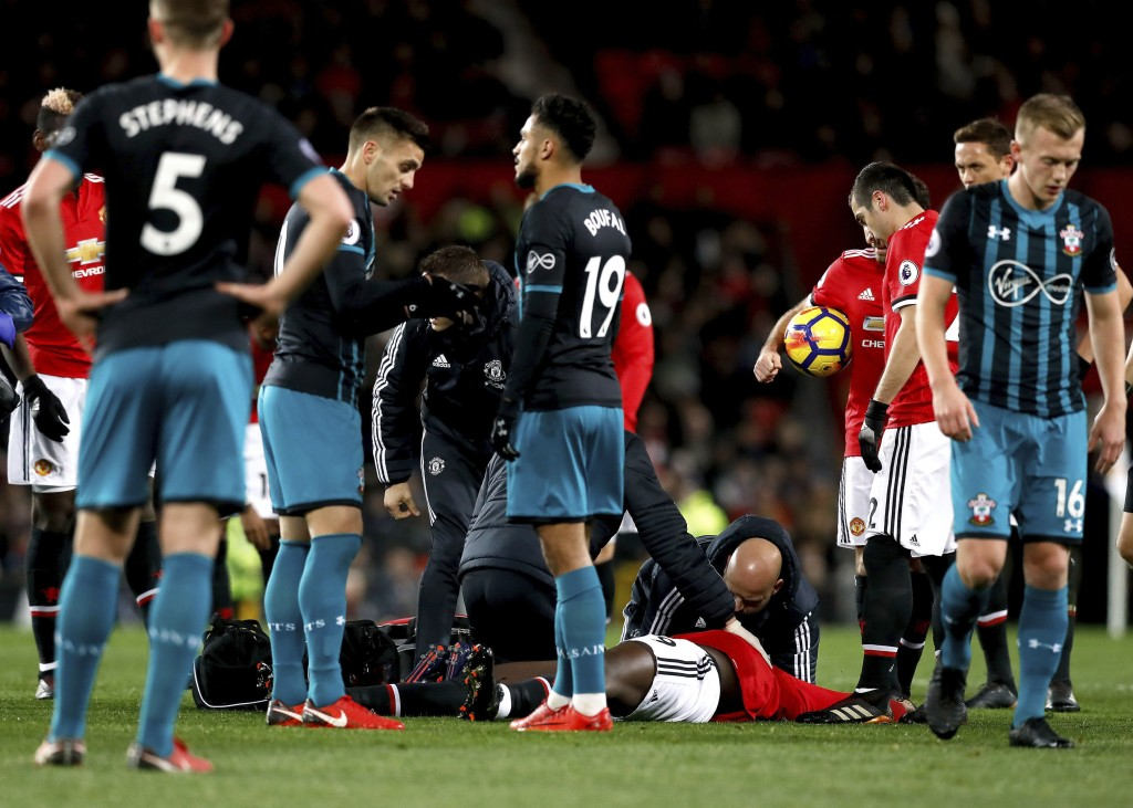 Manchester United's Romelu Lukaku receives treatment on the pitch after suffering a head injury during the English Premier League soccer match Manches...