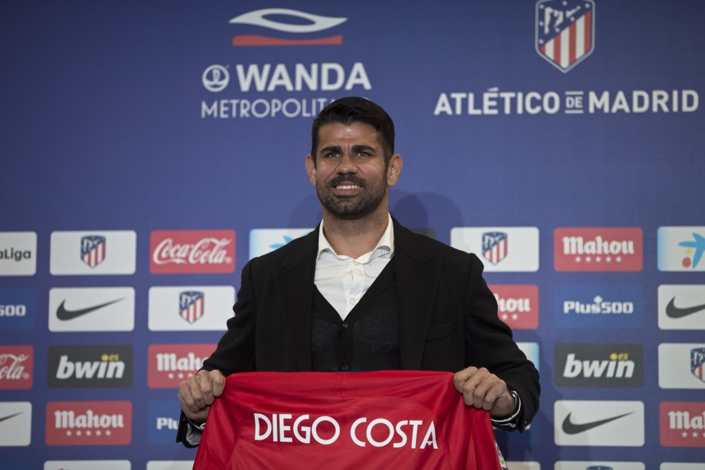 Diego Costa holds up his new shirt during his official presentation for Atletico Madrid at the Wanda Metropolitano stadium in Madrid, Spain, Sunday, D...