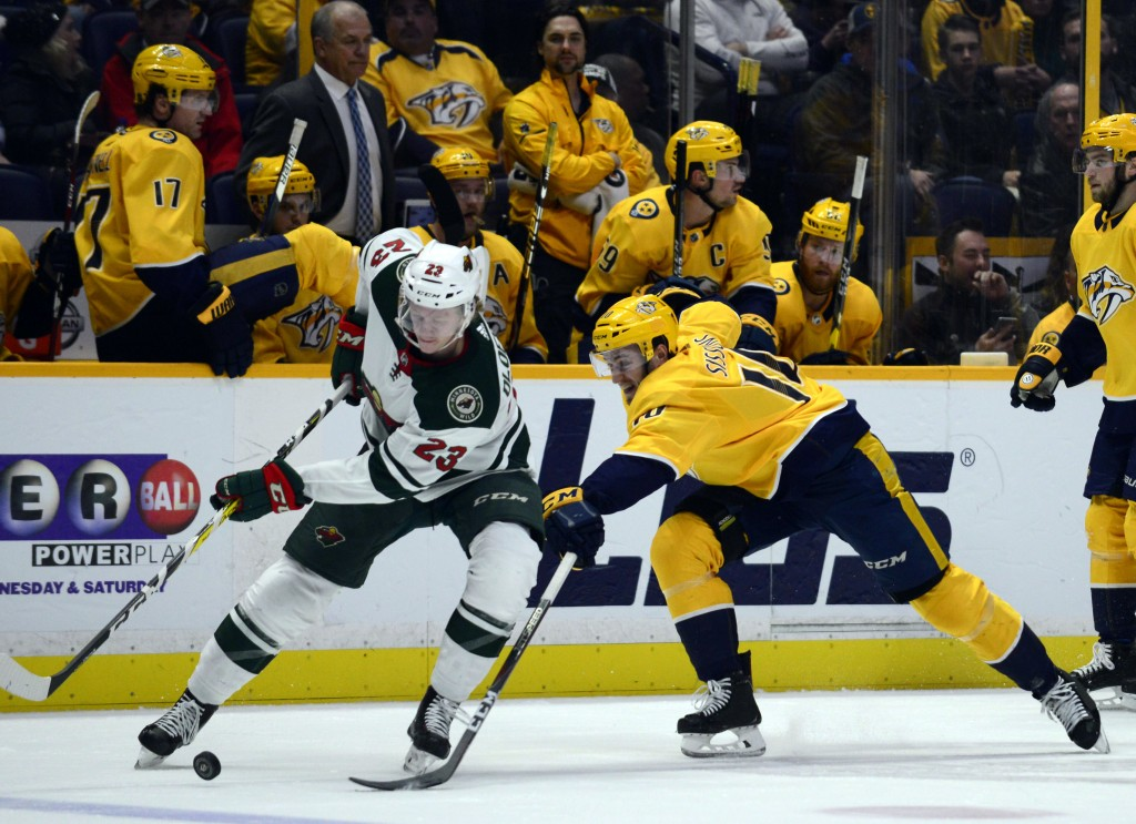Minnesota Wild defenseman Gustav Olofsson (23) and Nashville Predators center Colton Sissons (10) go after the puck in the second period of an NHL hoc...