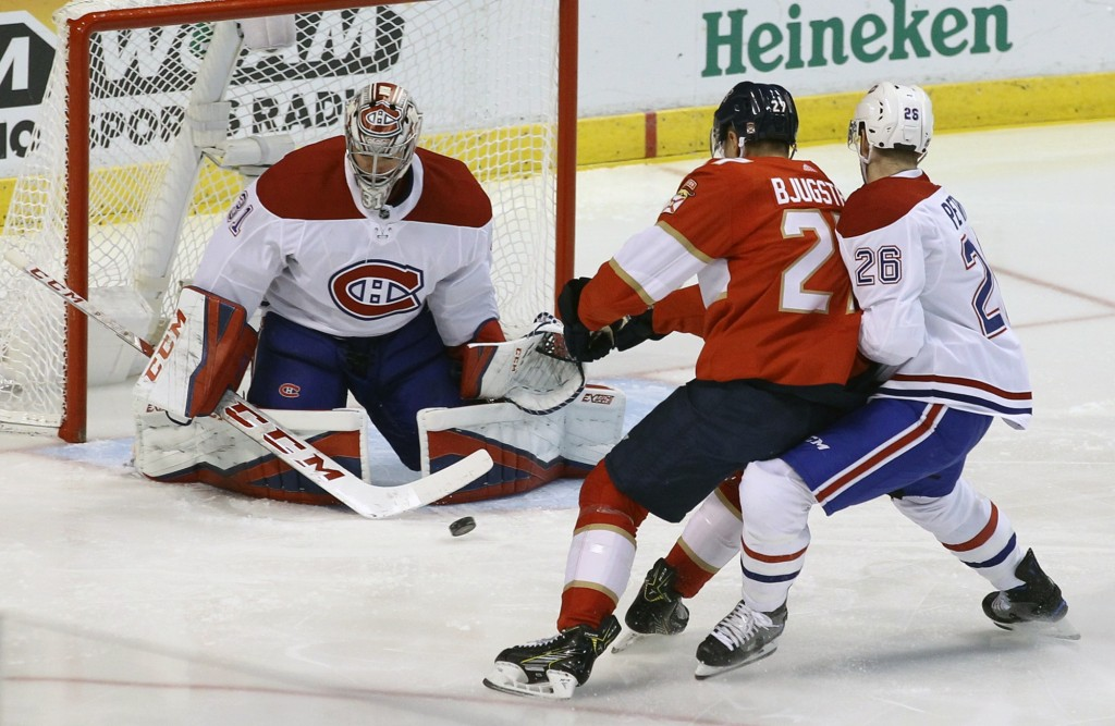Montreal Canadiens goalie Carey Price, left, blocks a shot from Florida Panthers' Nick Bjugstad, center, as Canadiens' Jeff Petry (26) defends during ...