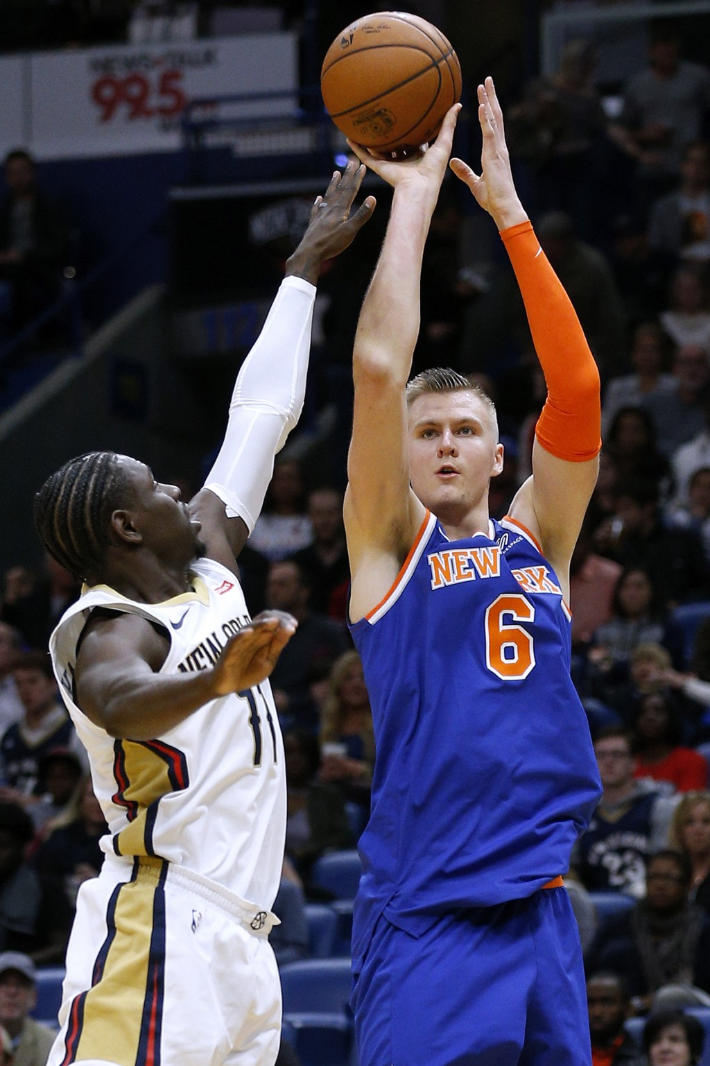 New York Knicks forward Kristaps Porzingis (6) shoots over New Orleans Pelicans guard Jrue Holiday (11) during the first half of an NBA basketball gam...