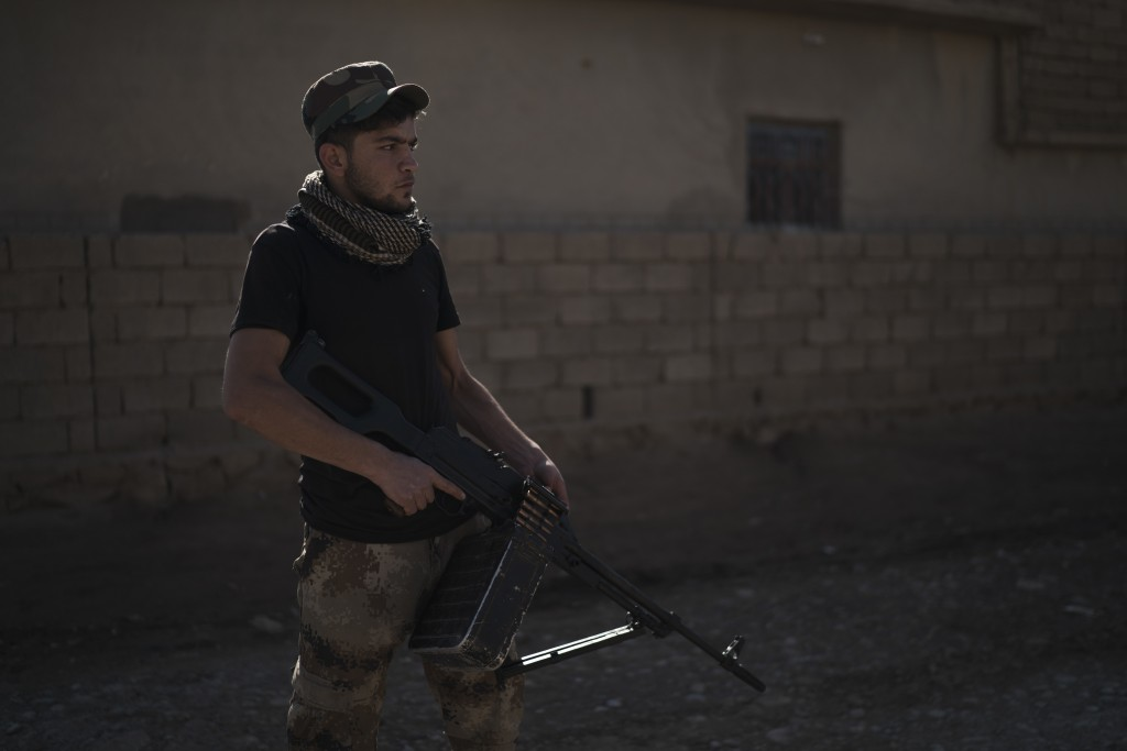 In this Nov. 12, 2017 photo, a local fighter stands on a street in the Bijwaniya village, south of Mosul, Iraq. Five young men were taken by unidentif...
